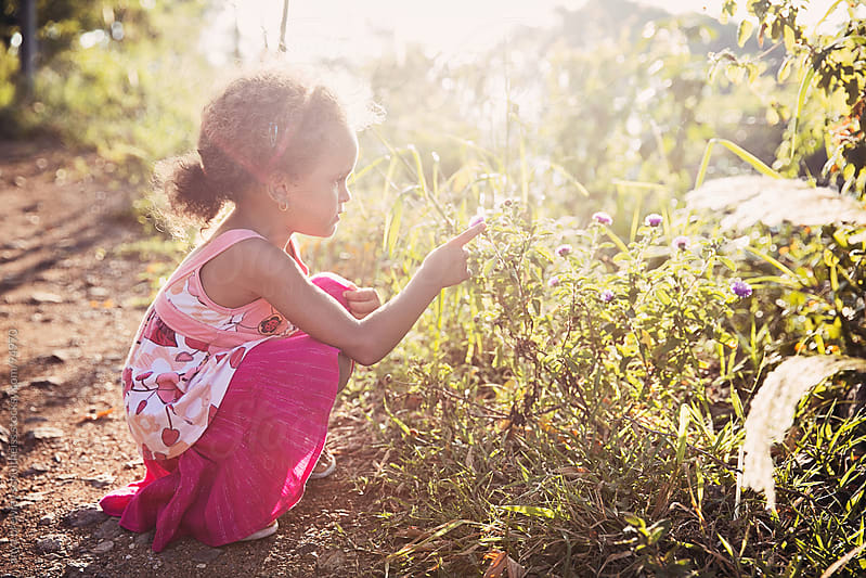 Portrait of a young girl admiring a flower on a warm summer day by anya brewley schultheiss for Stocksy United