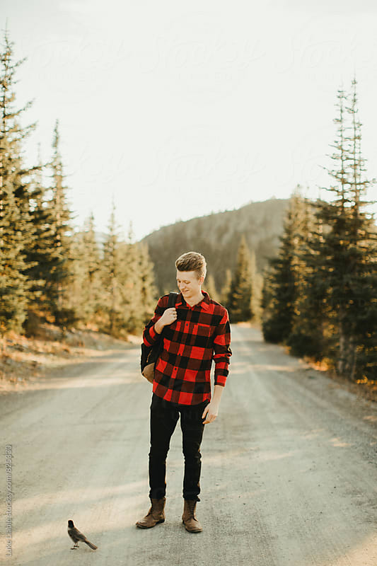Young man exploring mountain road with birds by Luke Liable for Stocksy United