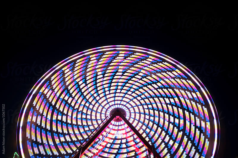 Spinning ferris wheel at night, abstract by Adam Nixon for Stocksy United