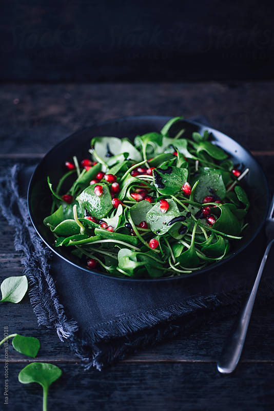 Food: winter purslane with pomegranate, balsamico and olive oil by Ina Peters for Stocksy United