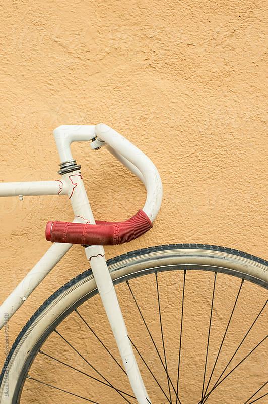 Closeup of a white vintage bicycle with red handlebars by Bisual Studio for Stocksy United