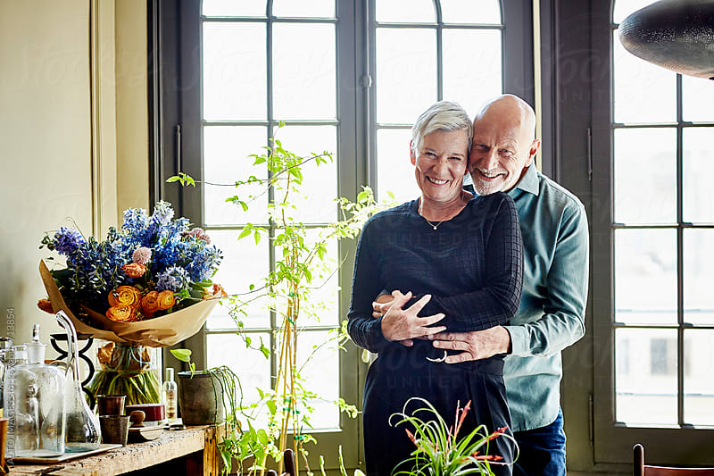 Smiling Senior Couple Embracing At Home by ALTO IMAGES for Stocksy United