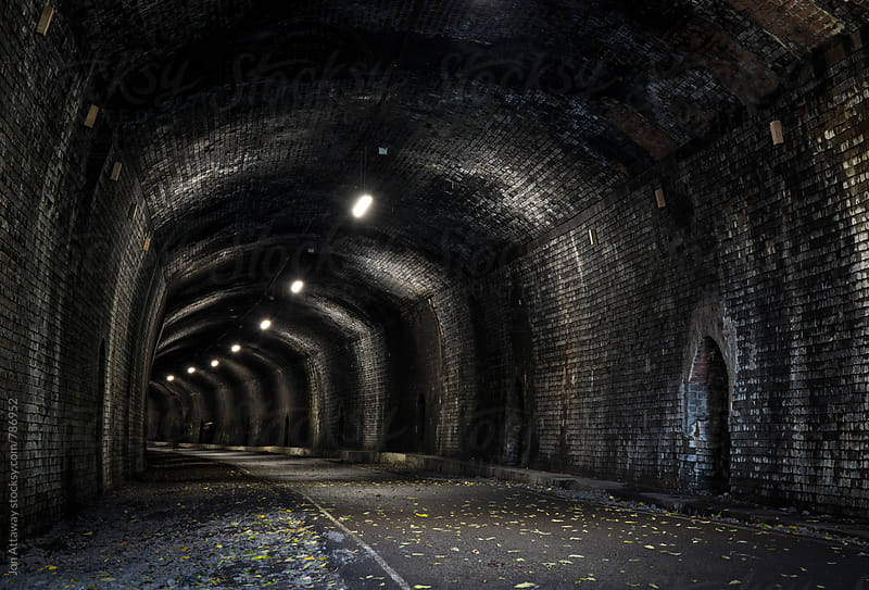 View into a dark old railway tunnel by Jon Attaway for Stocksy United