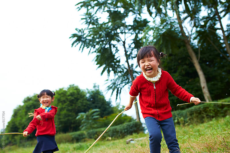 two lovely little asian girl having fun outdoor in the nature by Bo Bo for Stocksy United