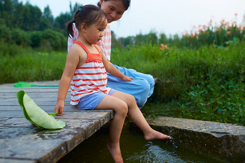 little girl sitting on the wooden bridge with her mother outdoor by Bo Bo for Stocksy United