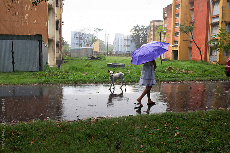 Teenage girl walking through a wet road with stray dog by PARTHA PAL for Stocksy United