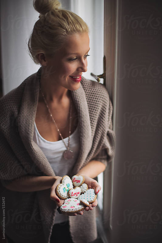 Woman Holding Heart-Shaped Cookies by Lumina for Stocksy United