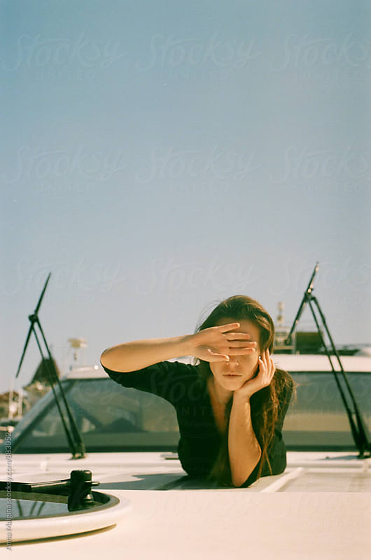 A film portrait of young beautiful woman closing her eyes on the yacht by Anna Malgina for Stocksy United
