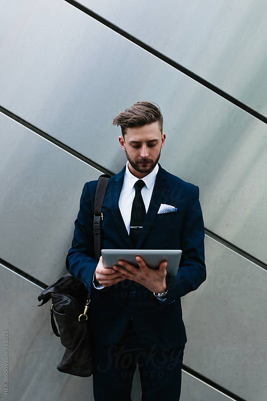 Young businessman using a digital tablet by HEX . for Stocksy United