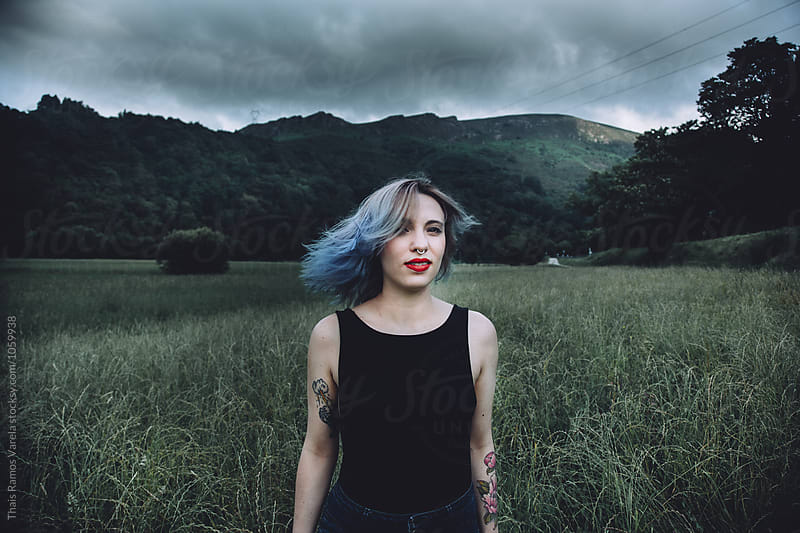 blue haired woman in a field by Thais Ramos Varela for Stocksy United