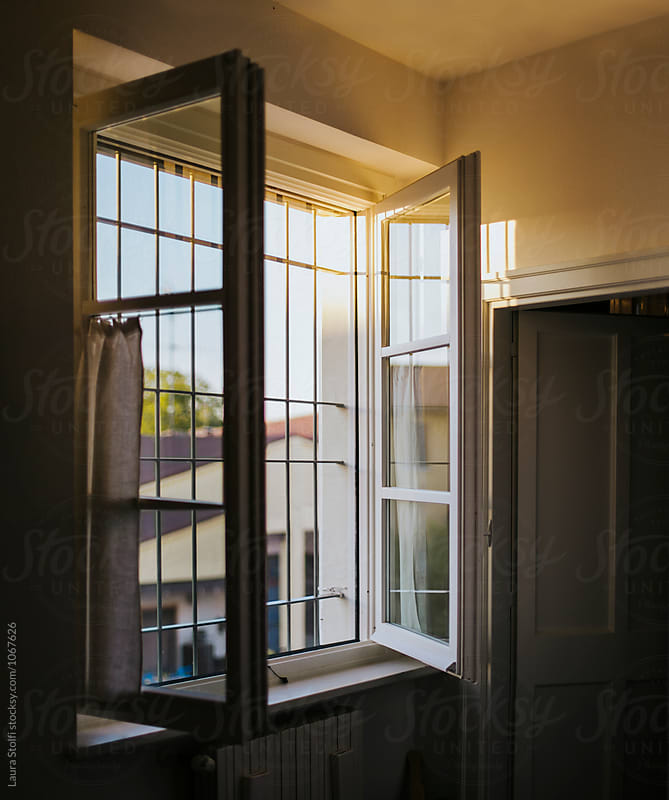 Sun setting through open window in summer evening by Laura Stolfi for Stocksy United