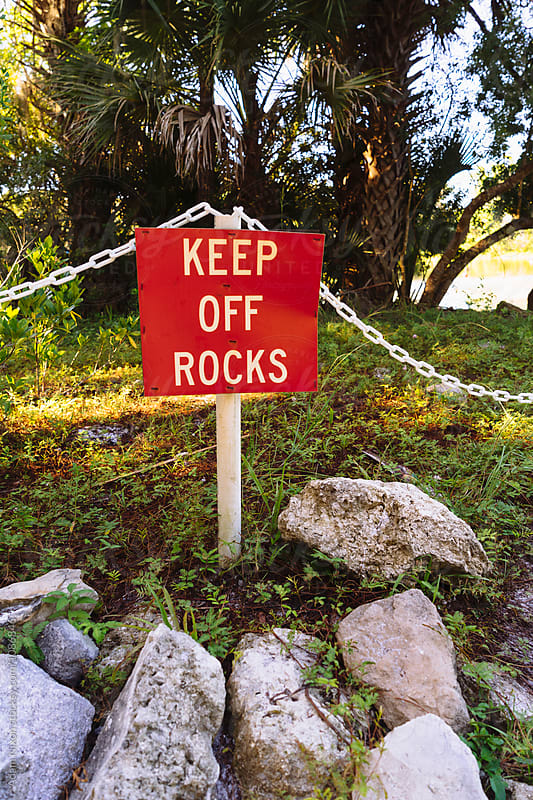 Keep Off Rocks warning sign by Adam Nixon for Stocksy United