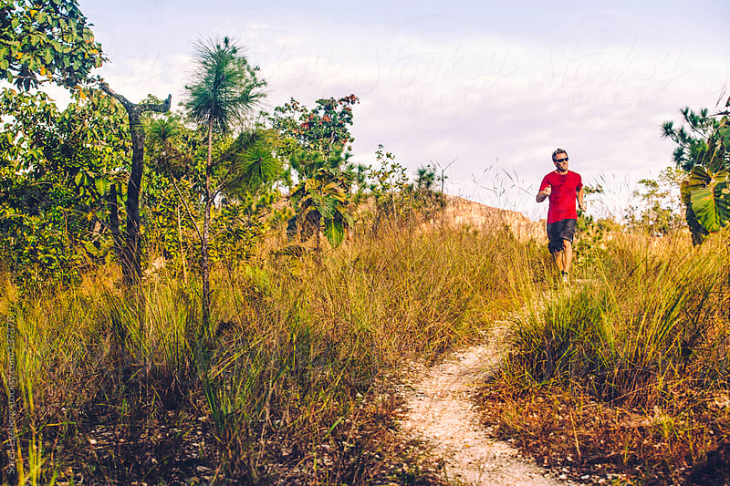 Man in red shirt running a nature trail outside in remote landsc by Soren Egeberg for Stocksy United