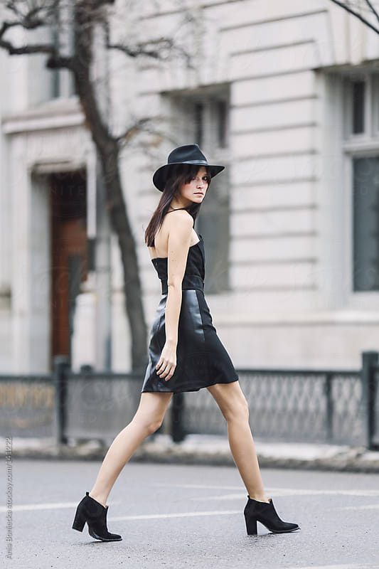 A beautiful woman in a black strapless mini dress crossing the street by Ania Boniecka for Stocksy United