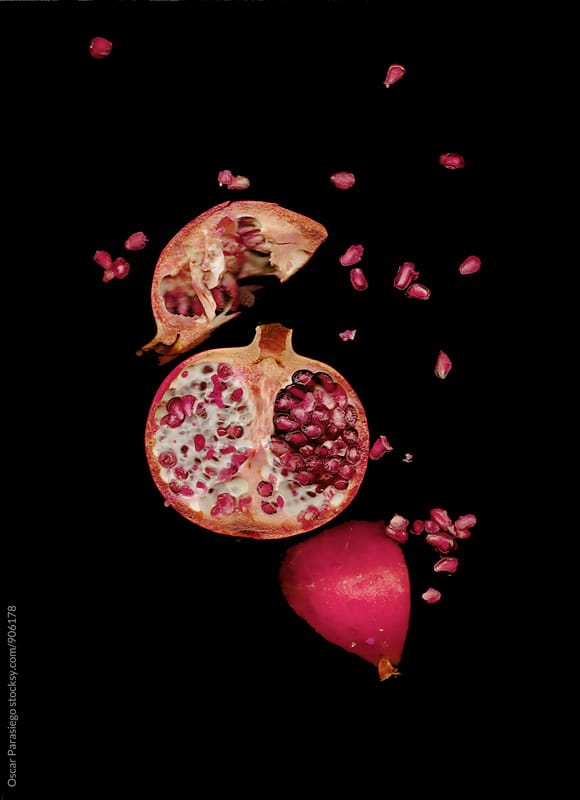Pomegranate in a black background by Oscar Parasiego for Stocksy United