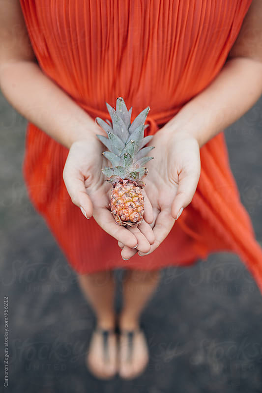young woman in red dress holding little pineapple by Cameron Zegers for Stocksy United