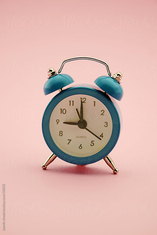 Alarm clock in blue on pink pastel background by Jasmin Awad for Stocksy United