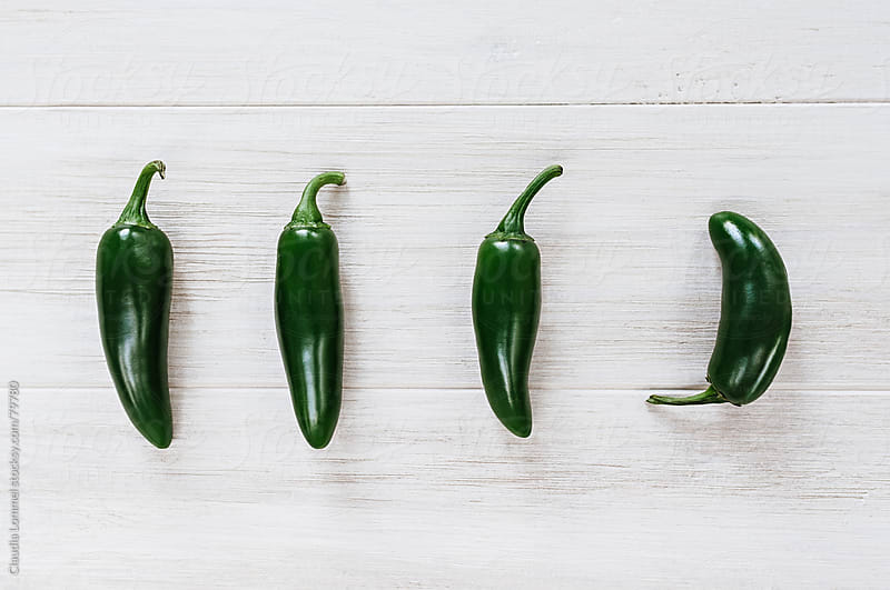 Four Green Chili Peppers Placed on a White Wooden Table by Claudia Lommel for Stocksy United