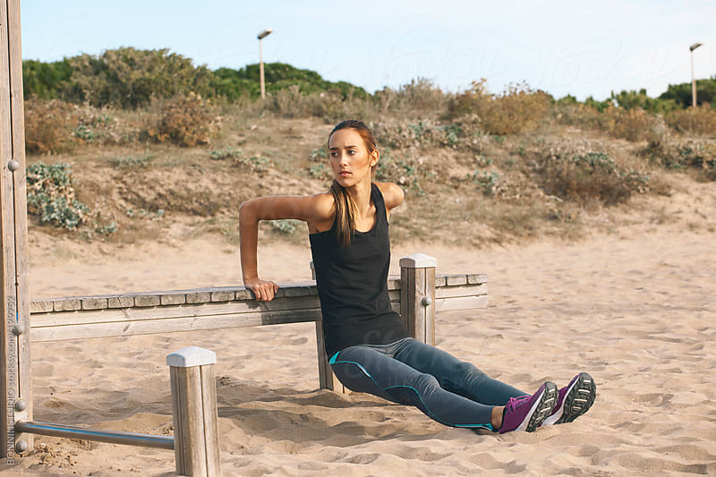 Fitness woman doing exercises of triceps in the beach. by BONNINSTUDIO for Stocksy United