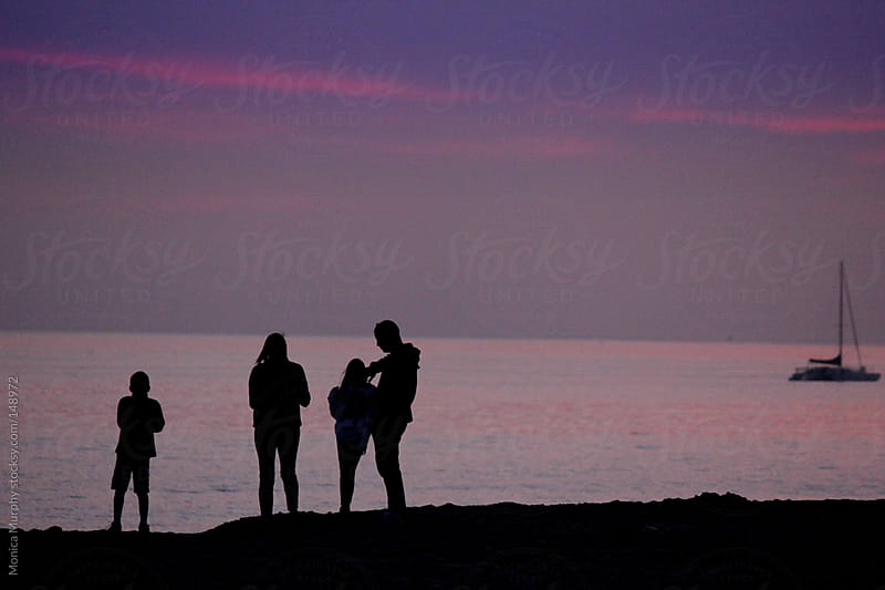 Silhouette of family standing by the ocean at sunset by Monica Murphy for Stocksy United