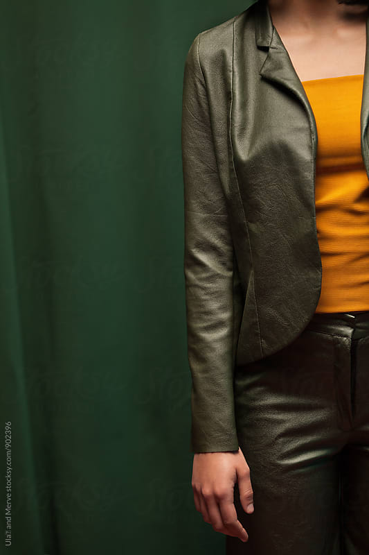 part of a lady wearing a faux leather green suit by Ulaş and Merve for Stocksy United