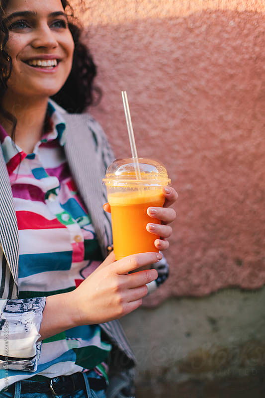 Happy woman drinking smoothie outdoors by VeaVea for Stocksy United