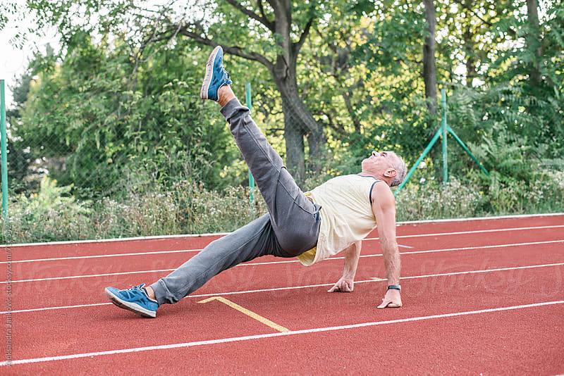 Senior Man Doing Exercise on the Racetrack by Aleksandra Jankovic for Stocksy United