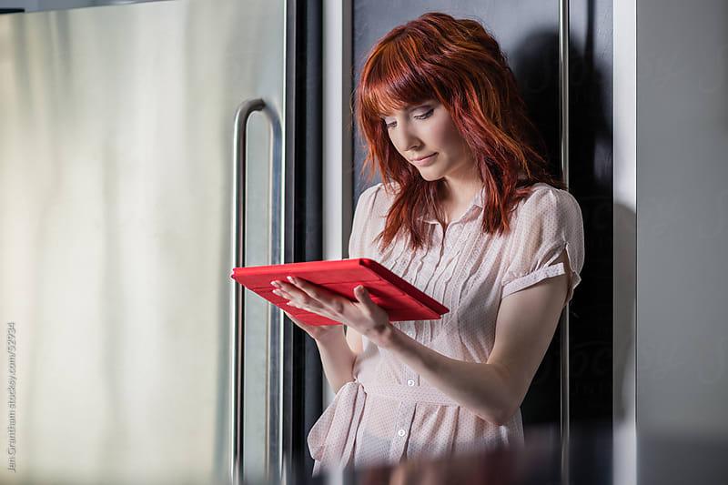 Woman using digital tablet in kitchen by Jen Grantham for Stocksy United