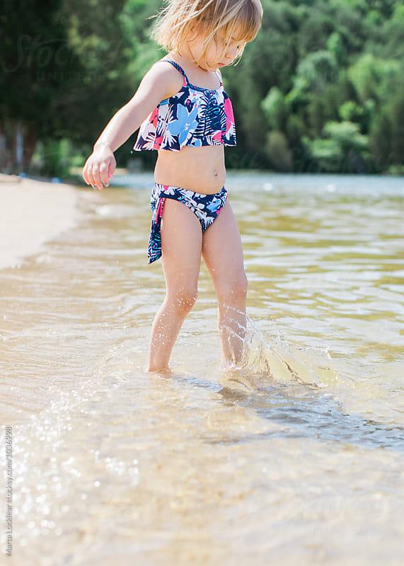 Girl splashing in the water by Marta Locklear for Stocksy United