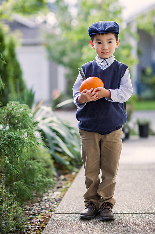 Asian boy holding a pumpkin by Suprijono Suharjoto for Stocksy United