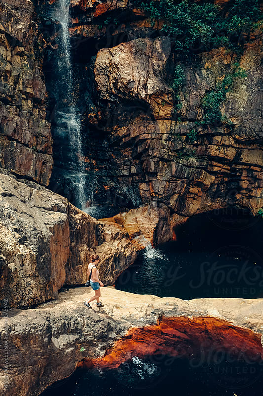 Woman walking near a waterfall by Micky Wiswedel for Stocksy United