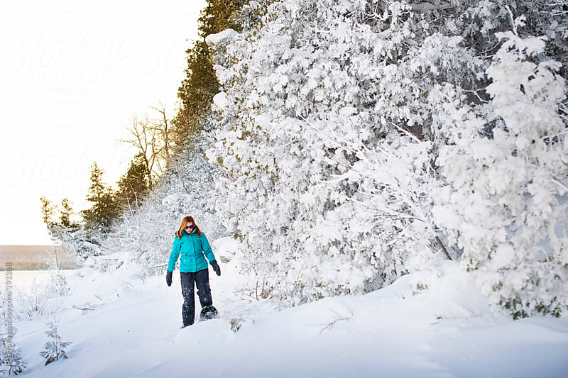 Woman Snowshoeing On Frozen Lakeshore With Snow Covered Trees by JP Danko for Stocksy United