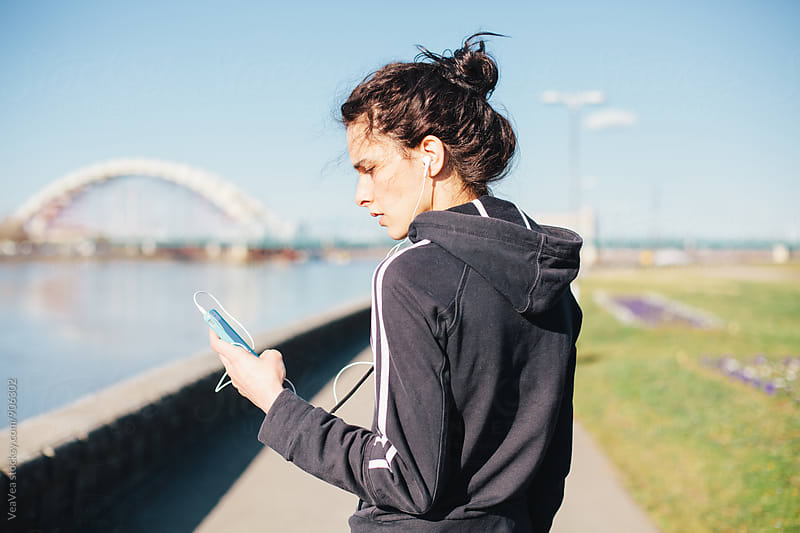 Woman in sportswear using her mobile phone outdoors by VeaVea for Stocksy United