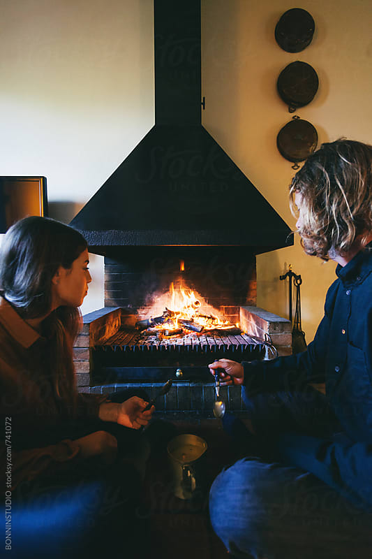 Couple eating a soup by the fireplace at home on winter. by BONNINSTUDIO for Stocksy United