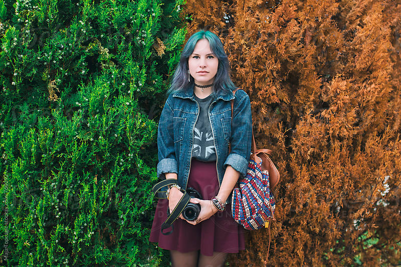 Young beautiful woman with blue hair in front of a half yellow, half green tree by Maja Topcagic for Stocksy United