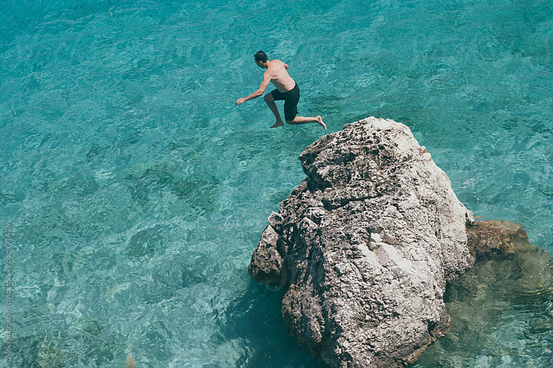 Man jumping from the rock into the sea by Aleksandra Jankovic for Stocksy United