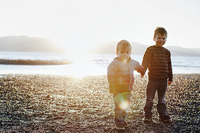 Two young boys holding hands on the beach at sunset by Rob and Julia Campbell for Stocksy United