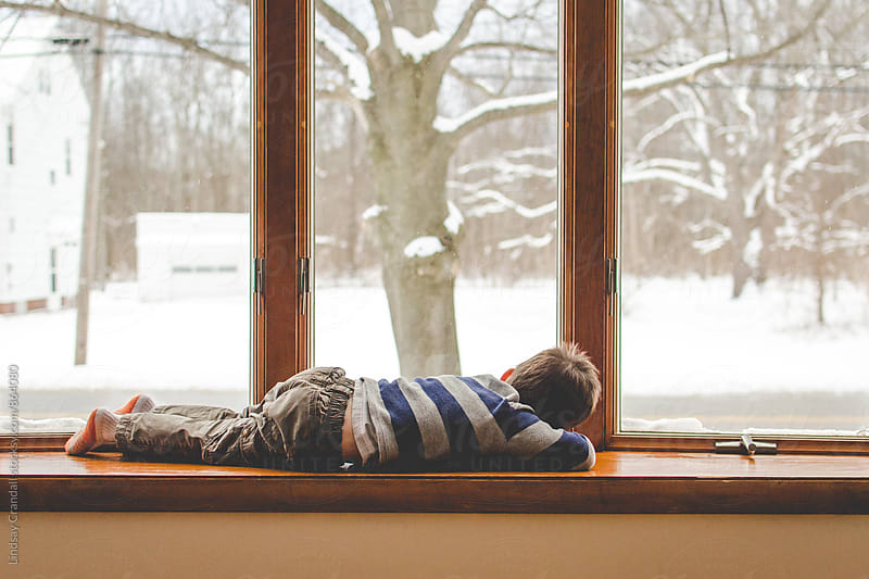 Boy lying beside a snowy window by Lindsay Crandall for Stocksy United