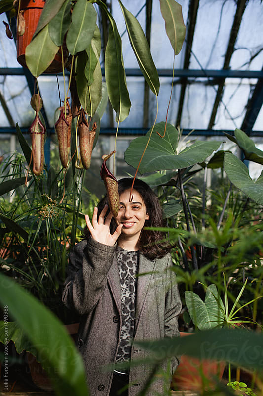 Woman laughs while touching phallic pitcher plants. by Julia Forsman for Stocksy United