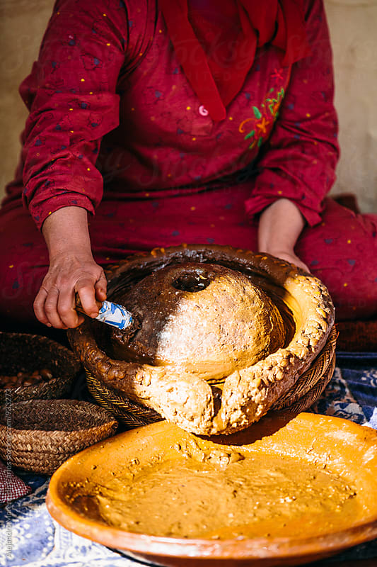 Woman making Argan oil crushing kernels with traditional tool by Alejandro Moreno de Carlos for Stocksy United
