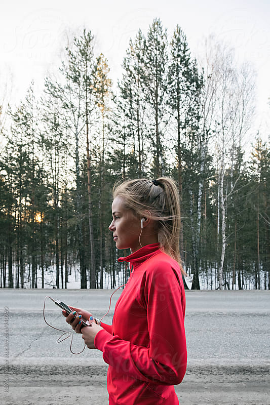 Side view of young sportswoman listening to music by Danil Nevsky for Stocksy United