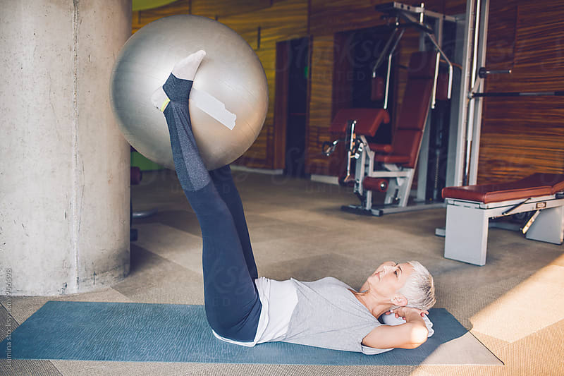 Woman Exercising with a Fit Ball in the Gym by Lumina for Stocksy United