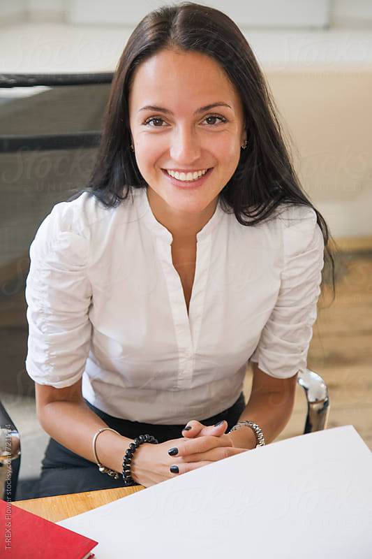 Smiling business woman in the office by Danil Nevsky for Stocksy United