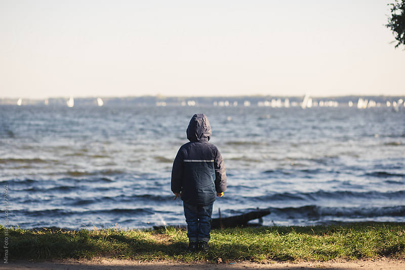 Boy in coat at lake, watching boats by Mima Foto for Stocksy United