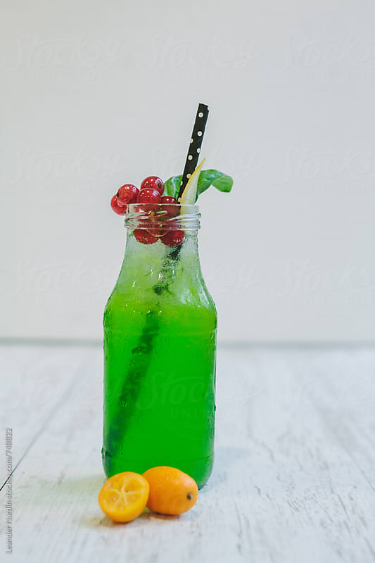 bilious green basil lemon cocktail with colorful fruit garnish by Leander Nardin for Stocksy United