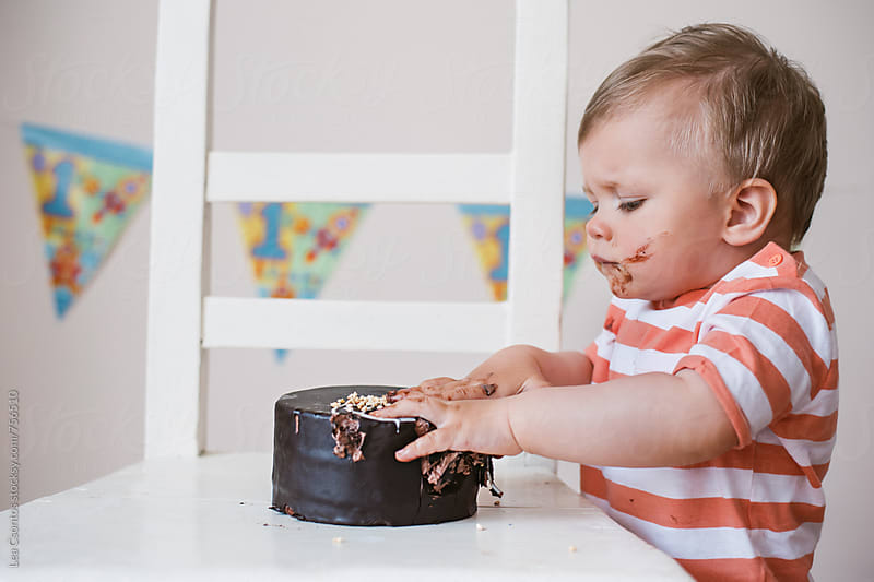 Portrait of a little boy just starting to smash his birthday cake by Lea Csontos for Stocksy United