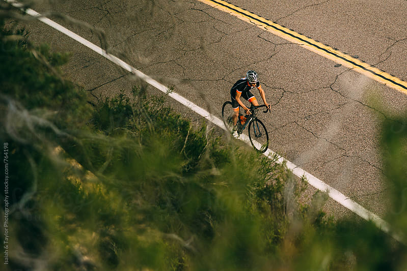 Man riding his bike on an open road in the mountains by Isaiah & Taylor Photography for Stocksy United