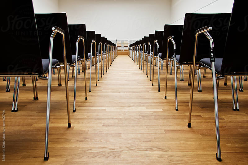 Row of chairs in empty convention room by Melanie Kintz for Stocksy United