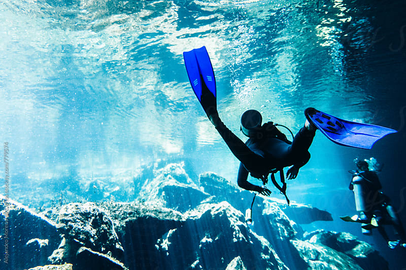 Back view of a scuba diver diving in a cenote in Yucatán, Mexico by Alejandro Moreno de Carlos for Stocksy United