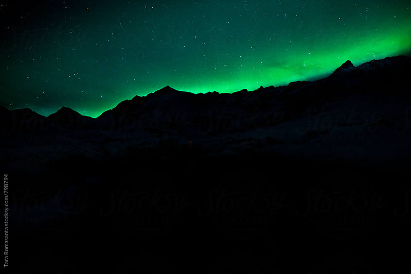 aurora borealis just above the ridge of a mountain by Tara Romasanta for Stocksy United